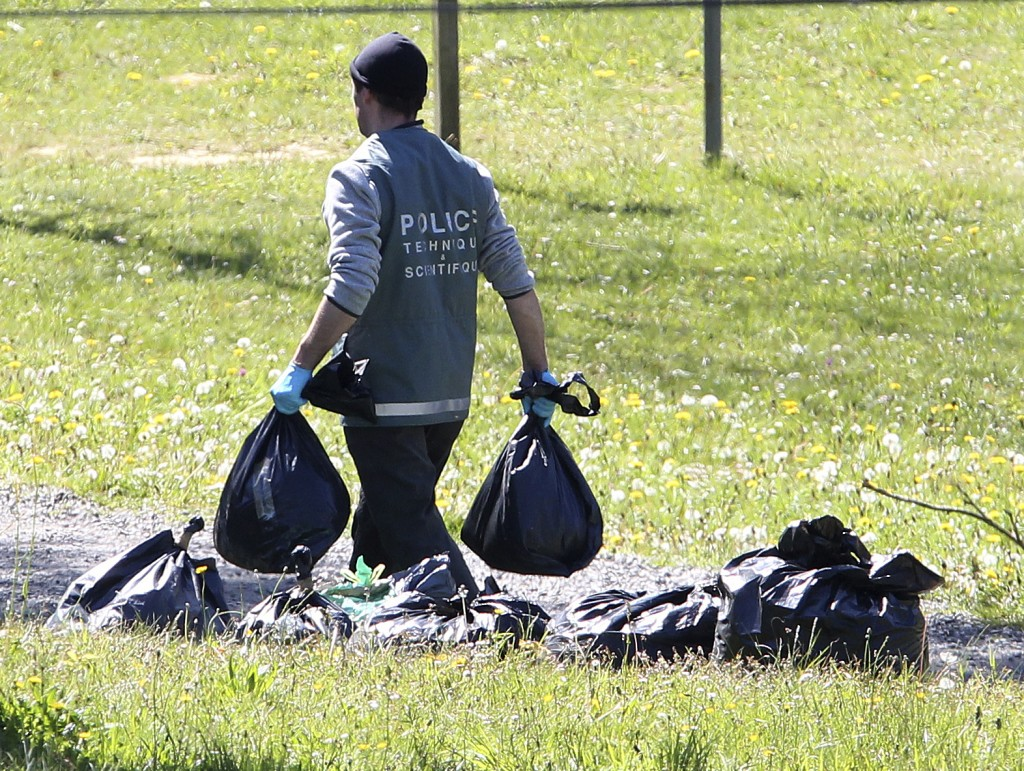 FILE - In this April 8, 2017 file photo, a French police officer collects plastic bags from a hideout used by Basque separatist guerrillas ETA in Sain...