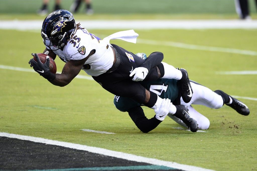 Baltimore Ravens' Gus Edwards (35) scores a touchdown as Philadelphia Eagles' Shaun Bradley (54) during the first half of an NFL football game, Sunday...