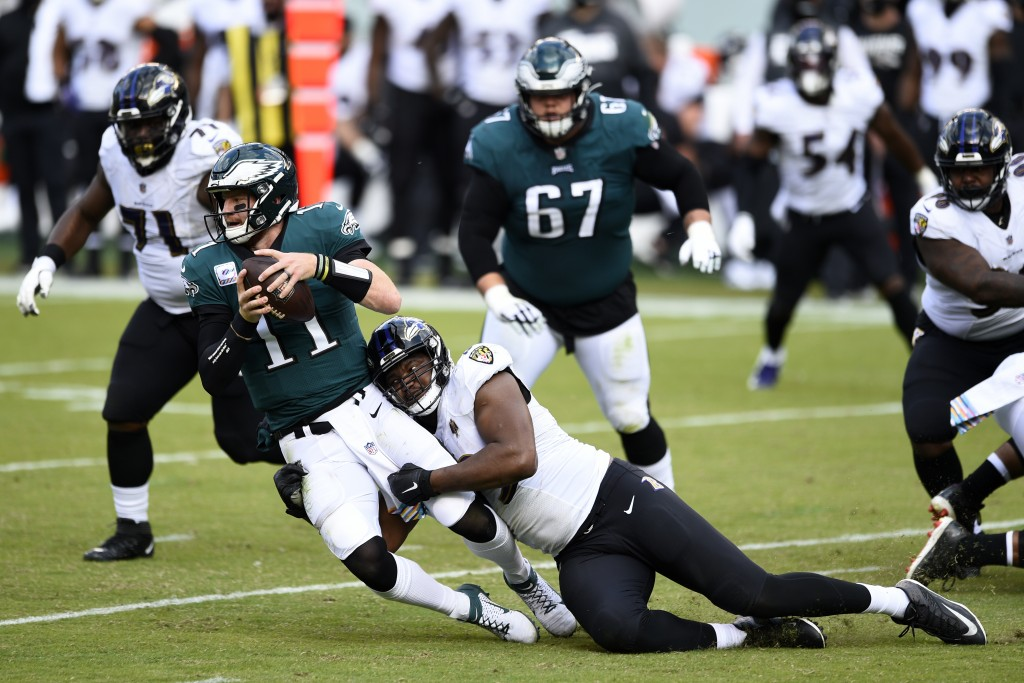 Philadelphia Eagles' Carson Wentz (11) is tackled by Baltimore Ravens' Calais Campbell (93) during the second half of an NFL football game, Sunday, Oc...