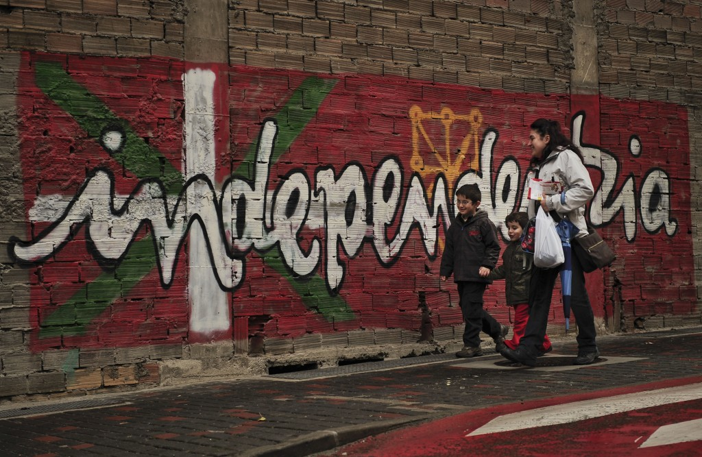 """FILE - In this Jan. 12, 2011 file photo, people walk past a wall with painted words in Basque that reads: """"Independence"""", in the small town of Alsasua..."""