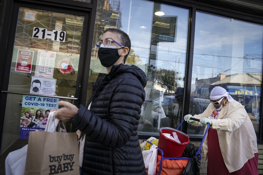 Pedestrians in protective masks pass a storefront on Thursday, Oct. 15, 2020, as restrictions on operations are imposed due to an increase in COVID-19...
