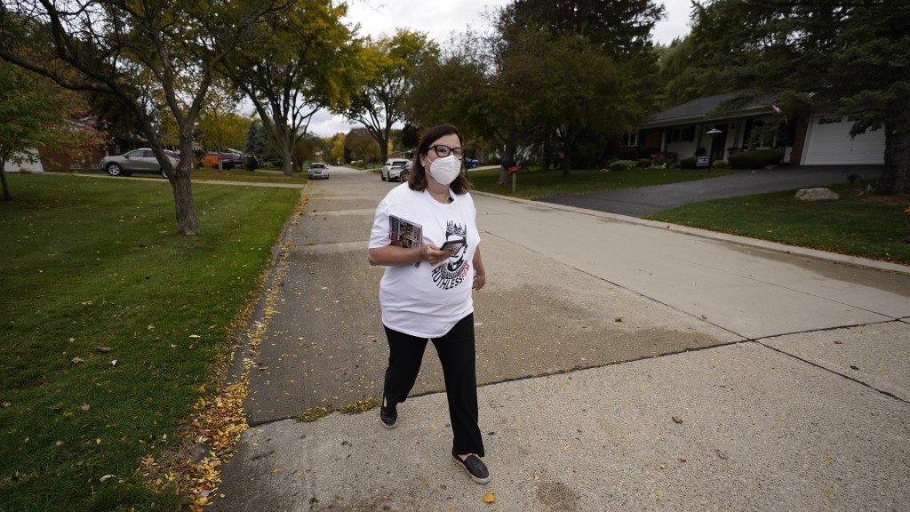 Lori Goldman walks between houses as she canvasses in Troy, Mich., Thursday, Oct. 15, 2020. Her Fems for Dems group has about 8,900 members. (AP Photo...