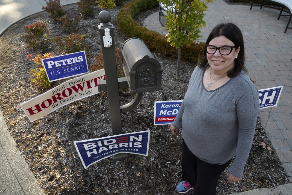 Lori Goldman poses for a portrait next to campaign signs outside her home in Bloomfield Village, Mich., Friday, Oct. 9, 2020. For most of her life, un...