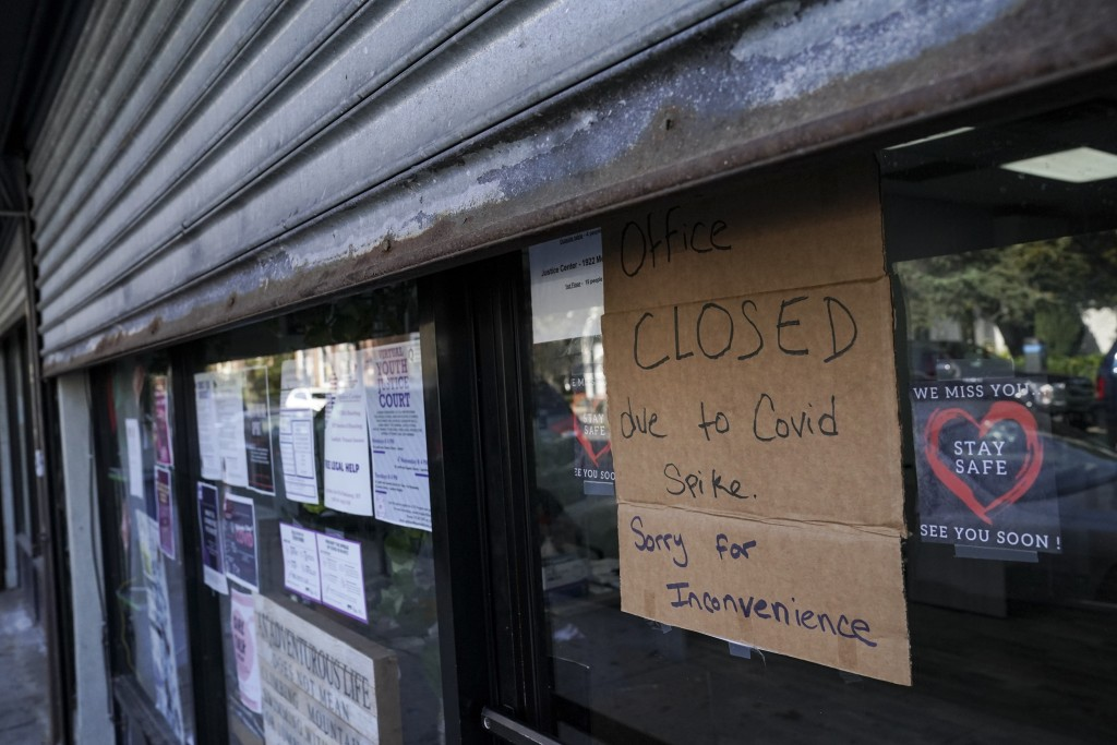 A storefront displays a closed sign as it remains shuttered due to a COVID-19 area infection rate increase, Thursday, Oct. 15, 2020, in the Far Rockaw...