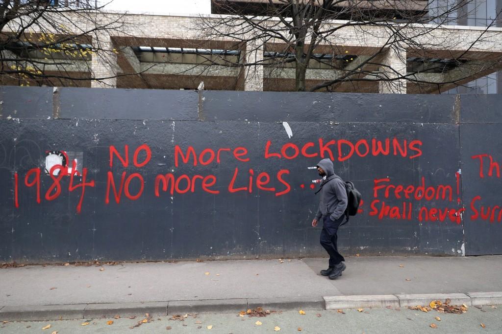 A man walks past anti-lockdown graffiti in Manchester, England, Monday, Oct. 19, 2020 as the row over Greater Manchester region's coronavirus status c...