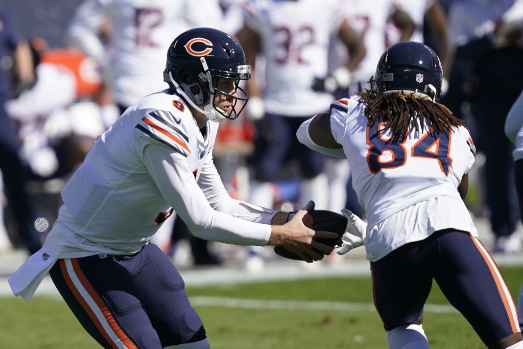 Chicago Bears quarterback Nick Foles (9) fakes a handoff to wide receiver Cordarrelle Patterson (84) during the first half of an NFL football game aga...