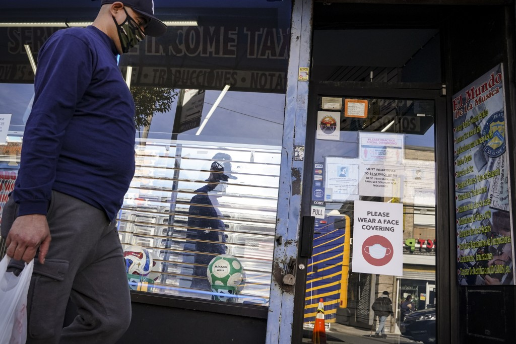 A pedestrian in a mask passes shuttered storefronts on Thursday, Oct. 15, 2020, as restrictions are imposed on the area due to an increase in COVID-19...