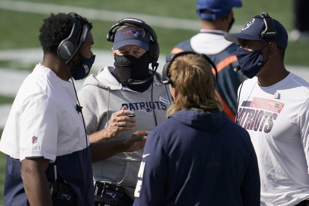 New England Patriots head coach Bill Belichick, center, consults with defensive coaches in the first half of an NFL football game against the Denver B...