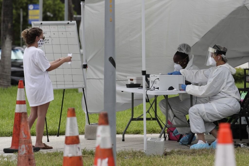 FILE - In this Friday, July 17, 2020 file photo, health care workers take information from people in line at a walk-up COVID-19 testing site during th...
