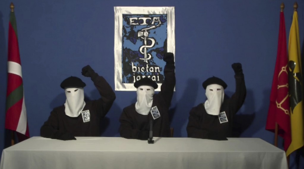 FILE - In this file image made from video provided on Oct. 20, 2011, masked members of the Basque separatist group ETA hold up their fists in unison f...