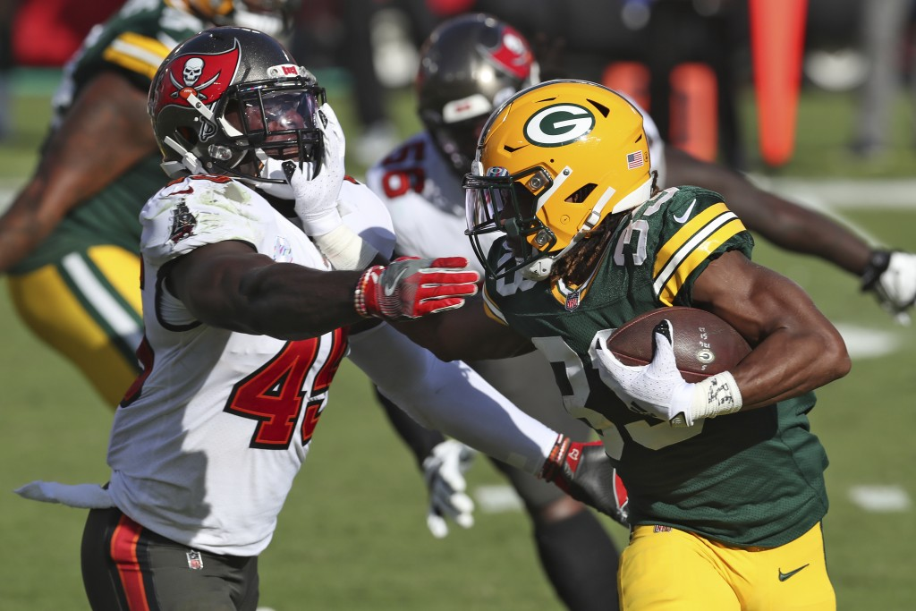 Green Bay Packers running back Aaron Jones (33) stiff arms Tampa Bay Buccaneers inside linebacker Devin White (45) during the first half of an NFL foo...