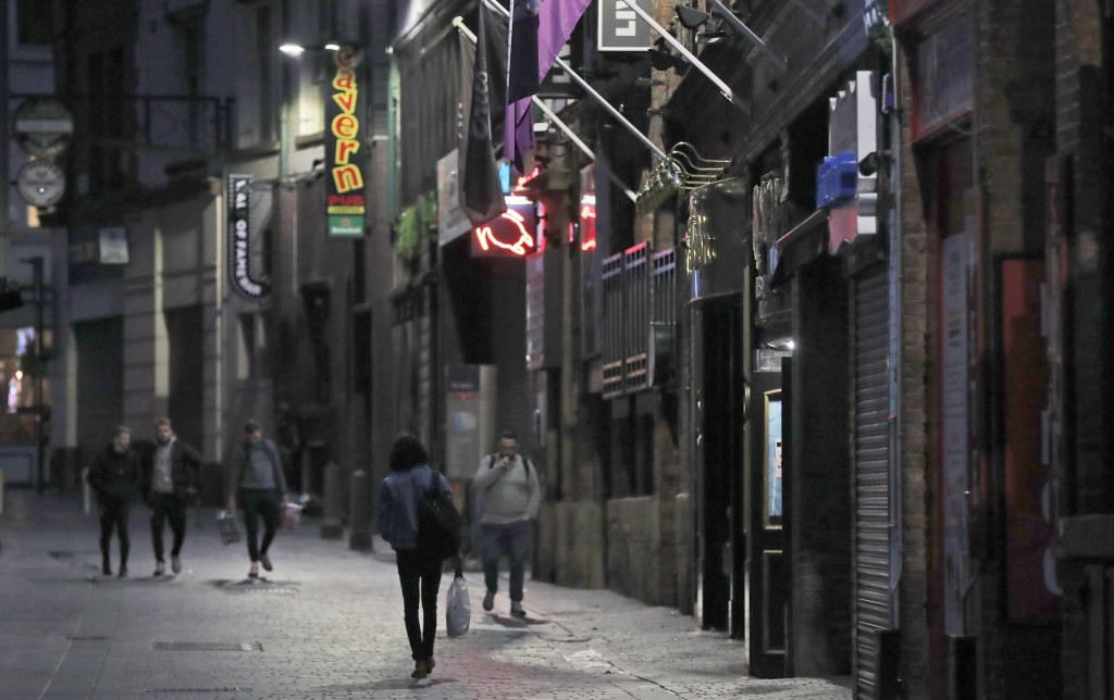 FILE - In this Oct. 14, 2020, file photo, people walk past closed bars as new measures across the region are set to come into force in Liverpool, Engl...