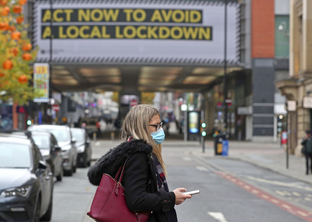 A woman wearing a face mask walks in Manchester, England, Monday, Oct. 19, 2020. Britain's government says discussions about implementing stricter res...