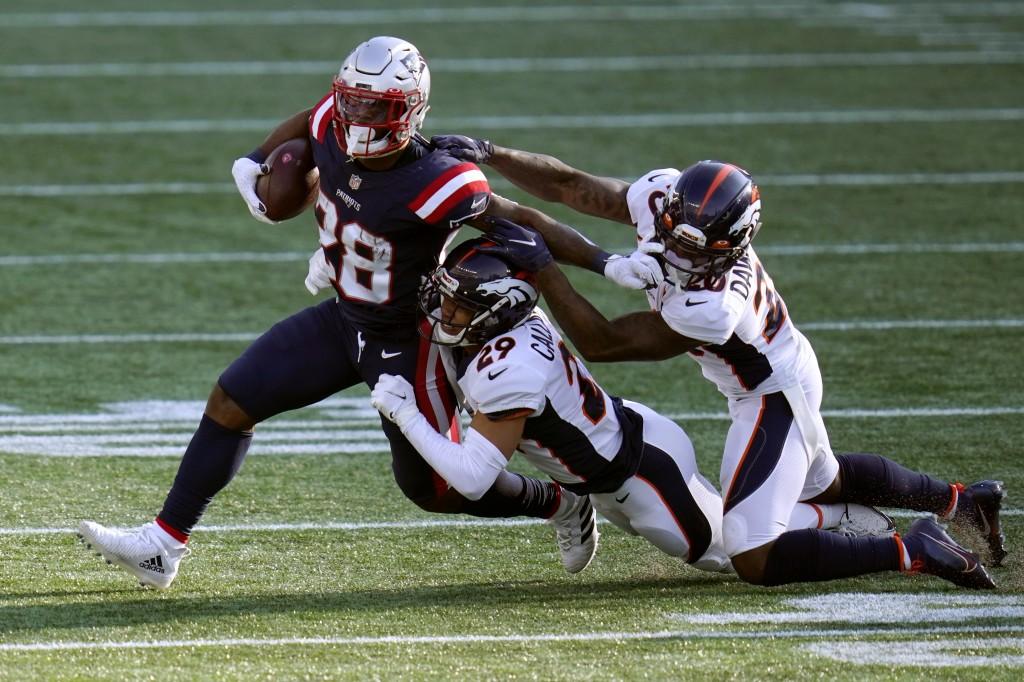 Denver Broncos cornerbacks Bryce Callahan (29) and Duke Dawson Jr. (20) tackle New England Patriots running back James White (28) in the second half o...