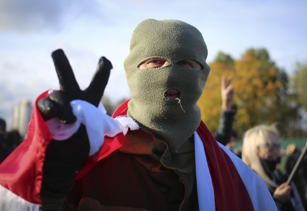 A masked protester gestures during an opposition rally to protest the official presidential election results in Minsk, Belarus, Sunday, Oct. 18, 2020....