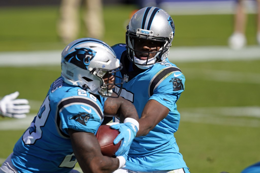 Carolina Panthers quarterback Teddy Bridgewater hands off to running back Mike Davis (28) during the second half of an NFL football game in Charlotte,...