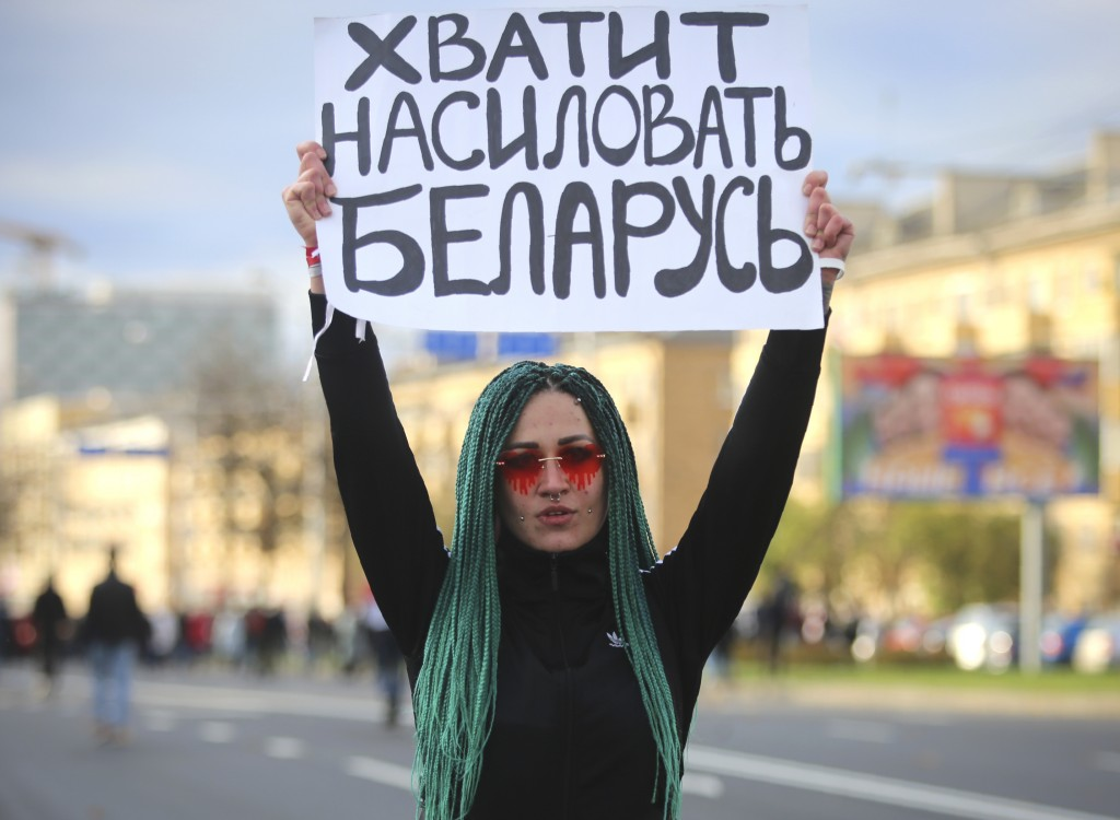 "A protester holds a sign reading ""Stop raping Belarus"" during an opposition rally to protest the official presidential election results in Minsk, Bela..."