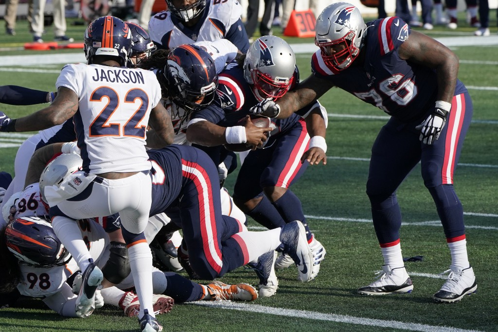 New England Patriots quarterback Cam Newton, center, bulls his way to the goal line and a touchdown in the second half of an NFL football game against...