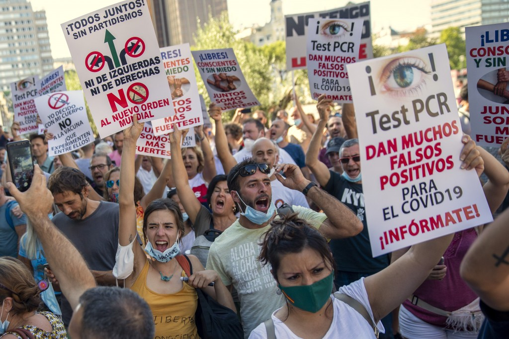 FILE - In this Aug. 16, 2020, file photo, demonstrators attend a protest against nationwide restrictions against COVID-19 in Madrid, Spain. Banners re...