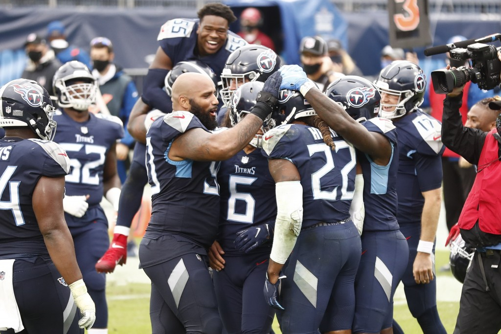 Tennessee Titans running back Derrick Henry (22) is mobbed by teammates after Henry scored the winning touchdown against the Houston Texans in overtim...