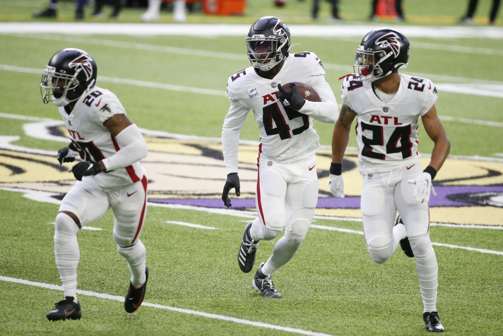 Atlanta Falcons linebacker Deion Jones, center, returns an interception with teammates Kendall Sheffield, left, and A.J. Terrell, right, during the fi...