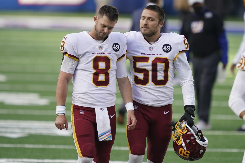 Washington Football Team quarterback Kyle Allen (8) is comforted by Jared Norris (50) after an NFL football game against the New York Giants, Sunday, ...