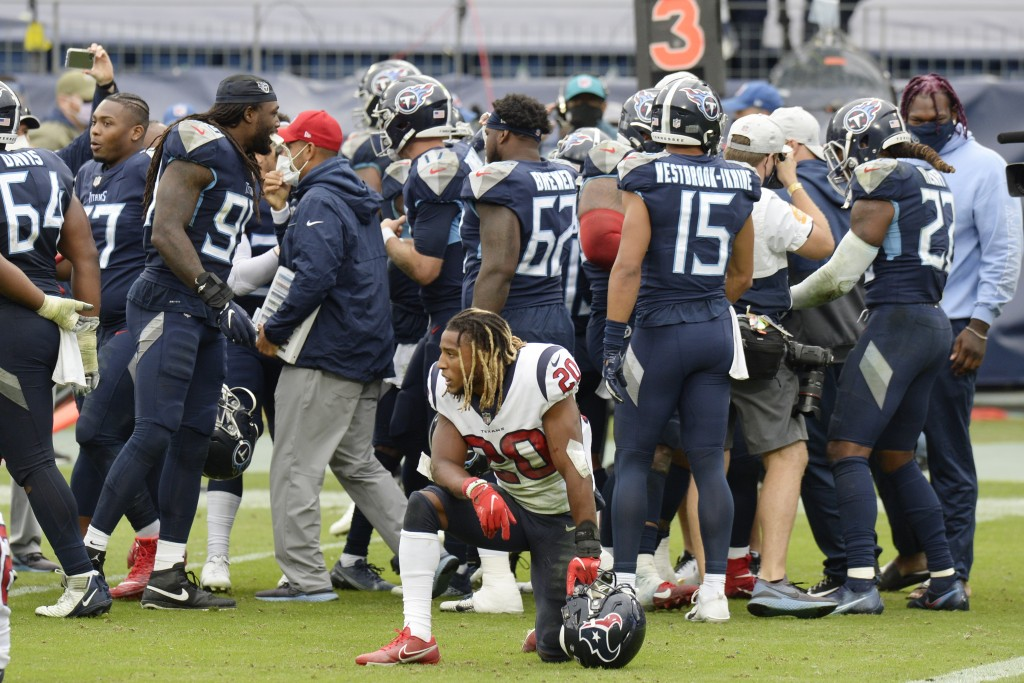 Houston Texans strong safety Justin Reid (20) kneels on the field as Tennessee Titans players celebrate after the Titans won 42-36 in overtime at an N...