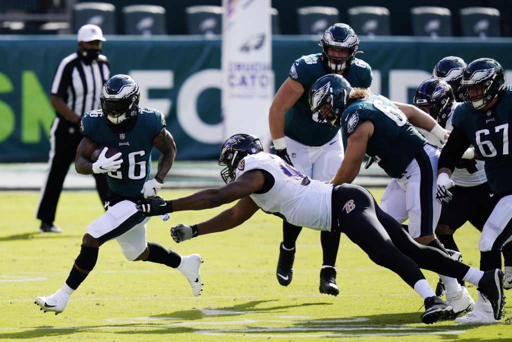 Philadelphia Eagles' Miles Sanders (26) runs past Baltimore Ravens' Calais Campbell (93) during the first half of an NFL football game, Sunday, Oct. 1...