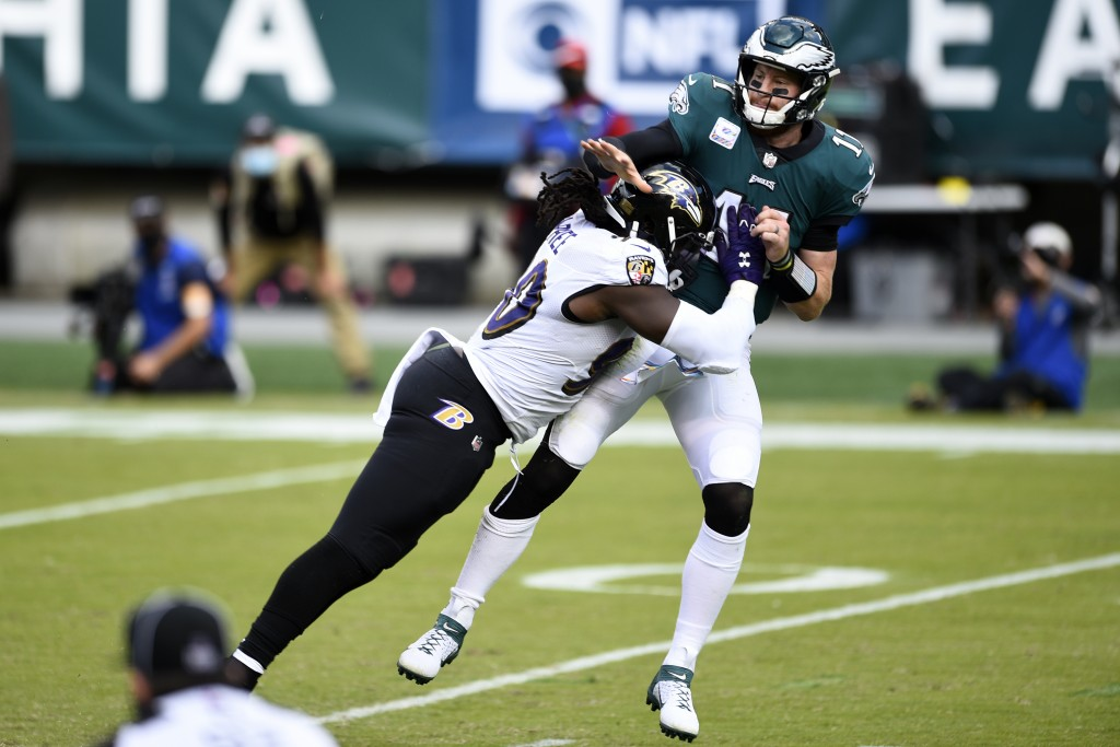 Philadelphia Eagles' Carson Wentz (11) is hit by Baltimore Ravens' Pernell McPhee (90) during the second half of an NFL football game, Sunday, Oct. 18...