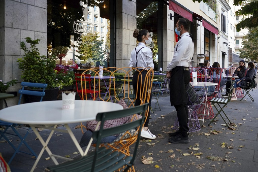 FILE - In this Oct. 13, 2020, file photo, a waiter and a waitress in masks wait for clients in Rome. After shutdowns swept nations during the first su...