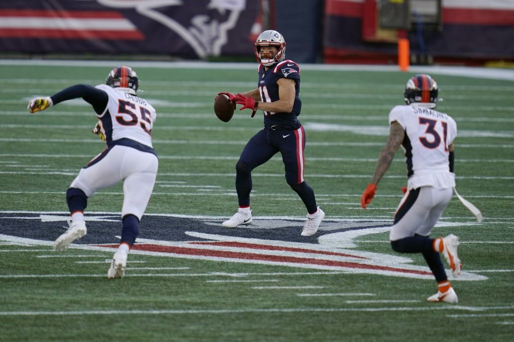 New England Patriots wide receiver Julian Edelman, center, looks for a receiver as he attempts to pass between Denver Broncos linebacker Bradley Chubb...