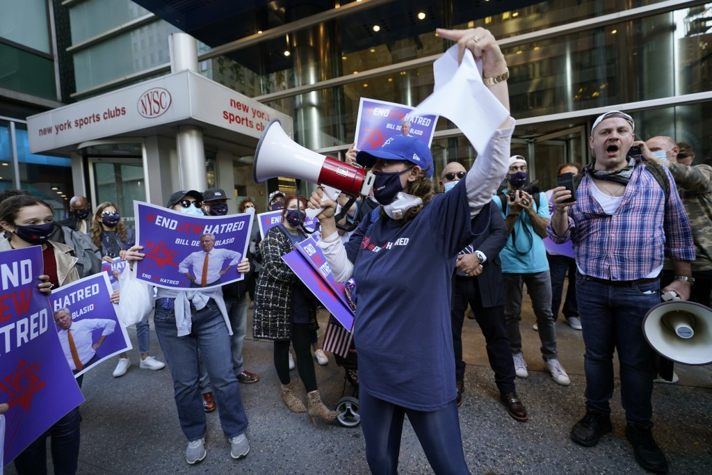 FILE - In this Oct. 15, 2020, file photo, protesters gather on the sidewalk outside the offices of New York Gov. Andrew Cuomo in New York. After shutd...