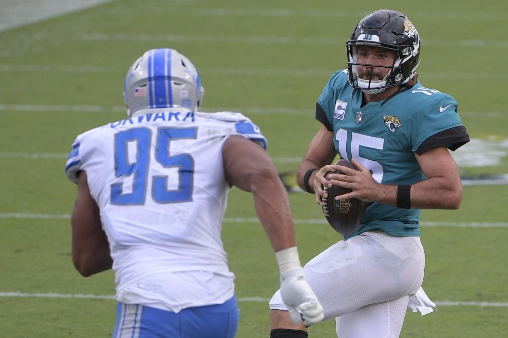 Jacksonville Jaguars quarterback Gardner Minshew II (15) looks for a receiver over Detroit Lions defensive end Romeo Okwara (95) during the second hal...