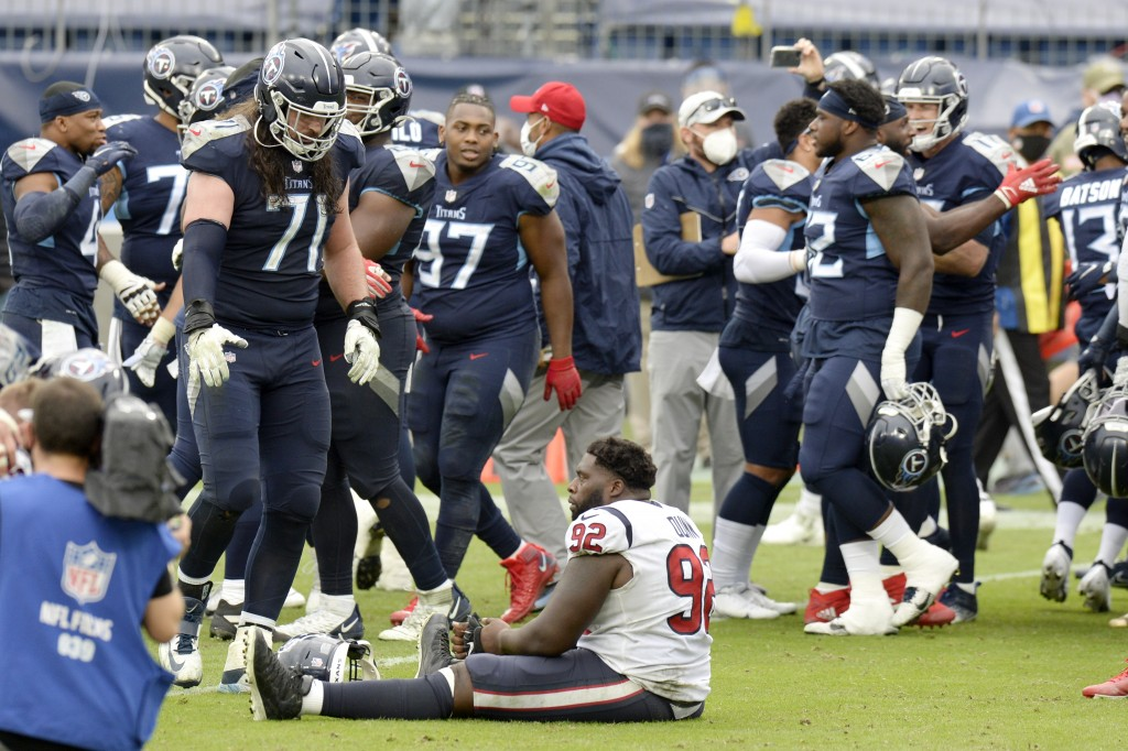 Houston Texans nose tackle Brandon Dunn (92) sits on the field as Tennessee Titans players celebrate after the Titans won 42-36 in overtime at an NFL ...