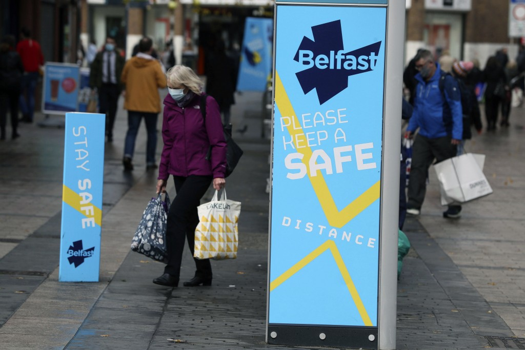 FILE - In this Oct. 14, 2020, file photo, a woman wears a face mask in central Belfast as Northern Ireland introduced the tightest COVID-19 restrictio...
