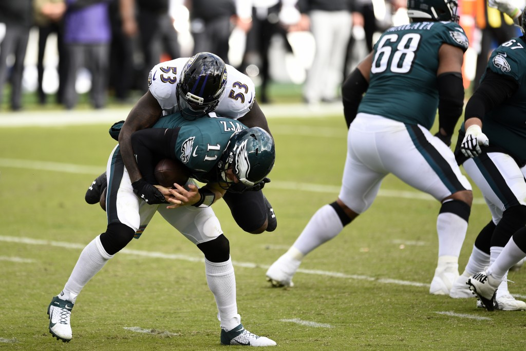 Philadelphia Eagles' Carson Wentz (11) is tackled by Baltimore Ravens' Jihad Ward (53) during the second half of an NFL football game, Sunday, Oct. 18...