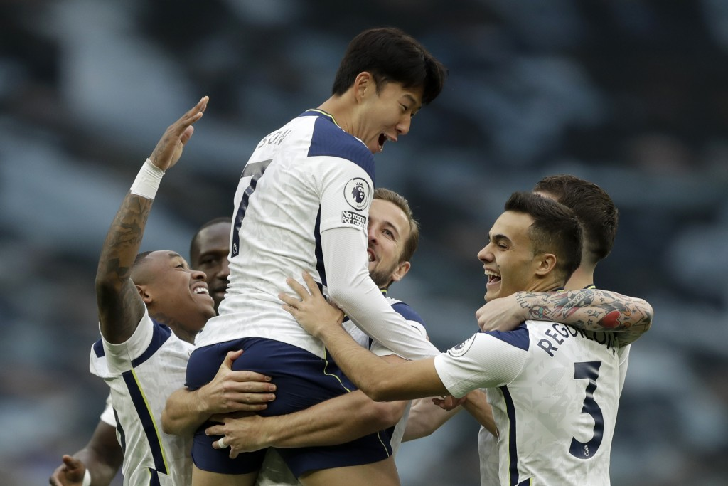 Tottenham's Son Heung-min celebrates in the arms of Harry Kane after scoring the opening goal during the English Premier League soccer match between T...