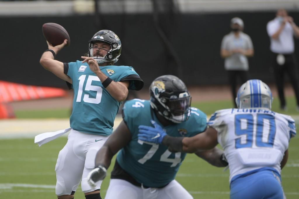 Jacksonville Jaguars quarterback Gardner Minshew II (15) throws a pass as offensive tackle Cam Robinson (74) blocks Detroit Lions defensive end Trey F...