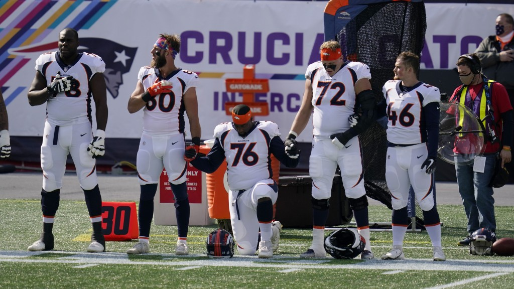 Members of the Denver Broncos team kneel and stand during the national anthem before an NFL football game against the New England Patriots, Sunday, Oc...