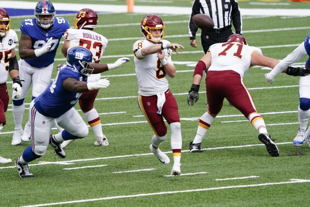 Washington Football Team's Kyle Allen (8) throws a pass away from New York Giants' Dalvin Tomlinson (94) during the first half of an NFL football game...