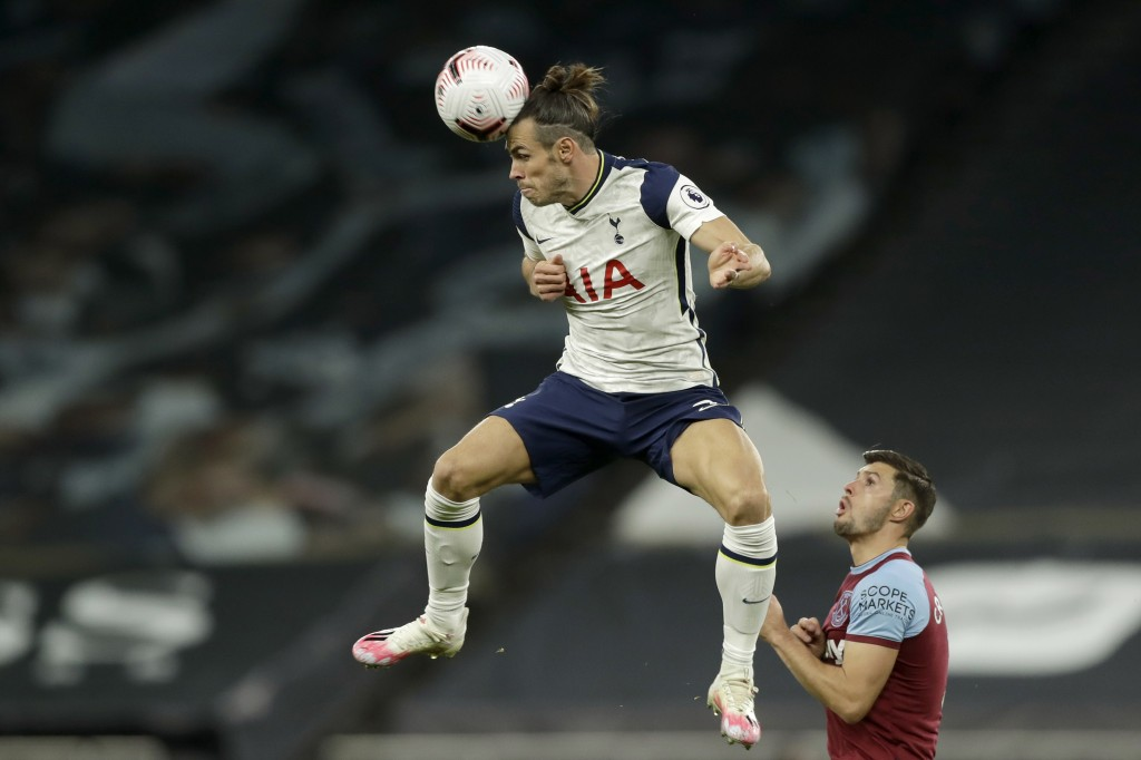 Tottenham's Gareth Bale heads the ball next to West Ham's Aaron Cresswell, right, during the English Premier League soccer match between Tottenham Hot...