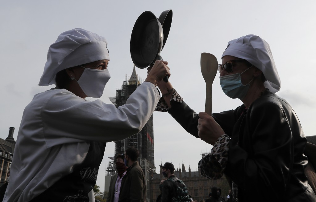 Hospitality workers beat their pans to protest in Parliament Square in London, Monday, Oct. 19, 2020. Hospitality workers are demonstrating outside Pa...