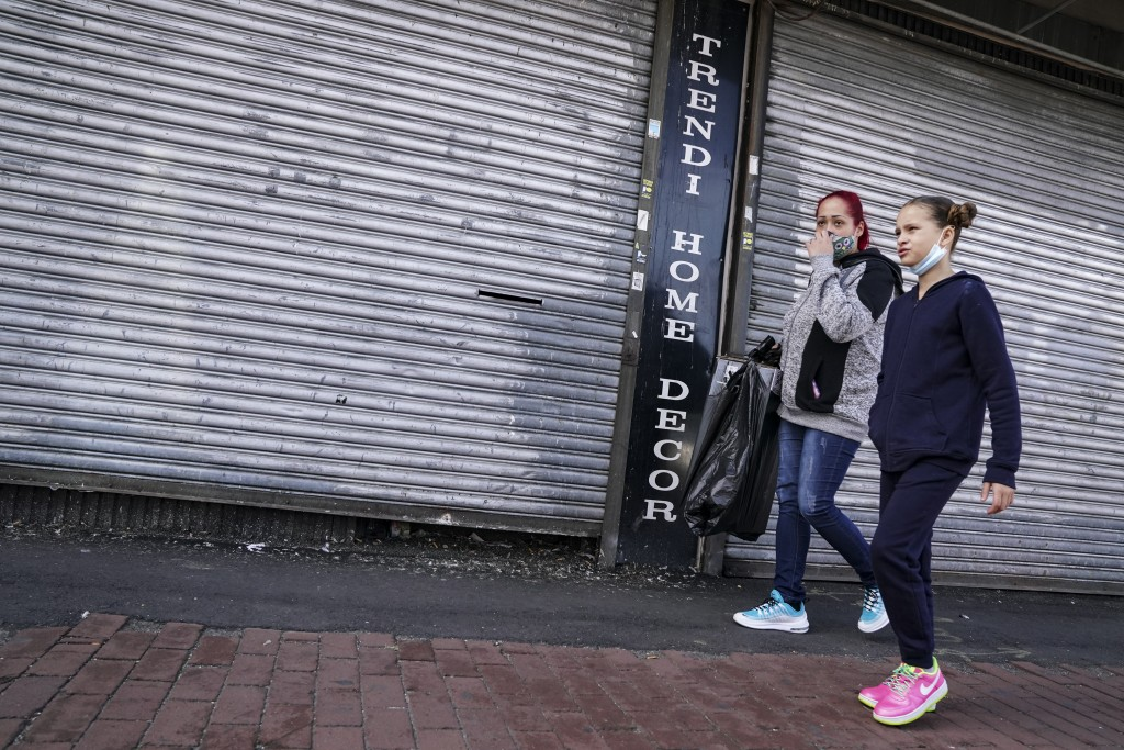 Pedestrians pass shuttered storefronts on Thursday, Oct. 15, 2020, as restrictions are imposed due to a COVID-19 infection increase in the Far Rockawa...