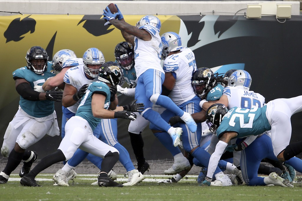 Detroit Lions running back D'Andre Swift, center, leaps over the line for a 1-yard touchdown against the Jacksonville Jaguars during the first half of...