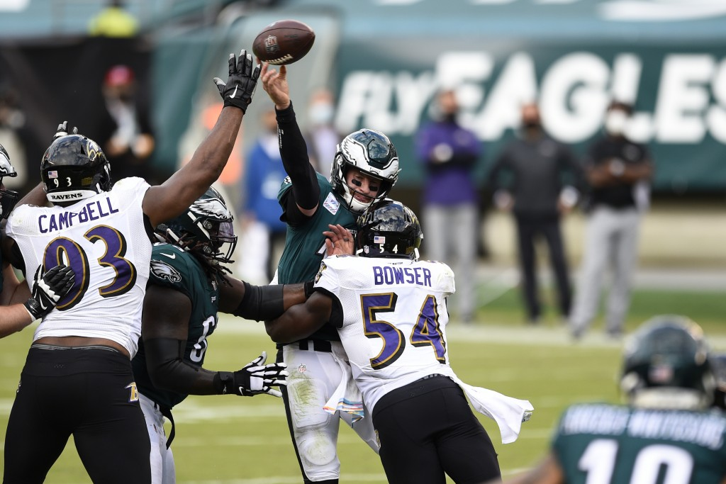 Philadelphia Eagles' Carson Wentz (11) tries to pass against Baltimore Ravens' Tyus Bowser (54) and Calais Campbell (93) during the second half of an ...