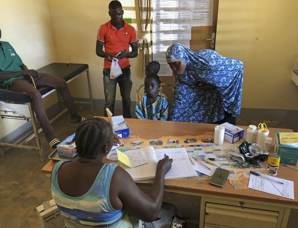 A boy sits in a chair and speaks to a nurse at a small clinic in Gampela village on the outskirts of Burkina Faso's capital, Ouagadougou on Saturday O...