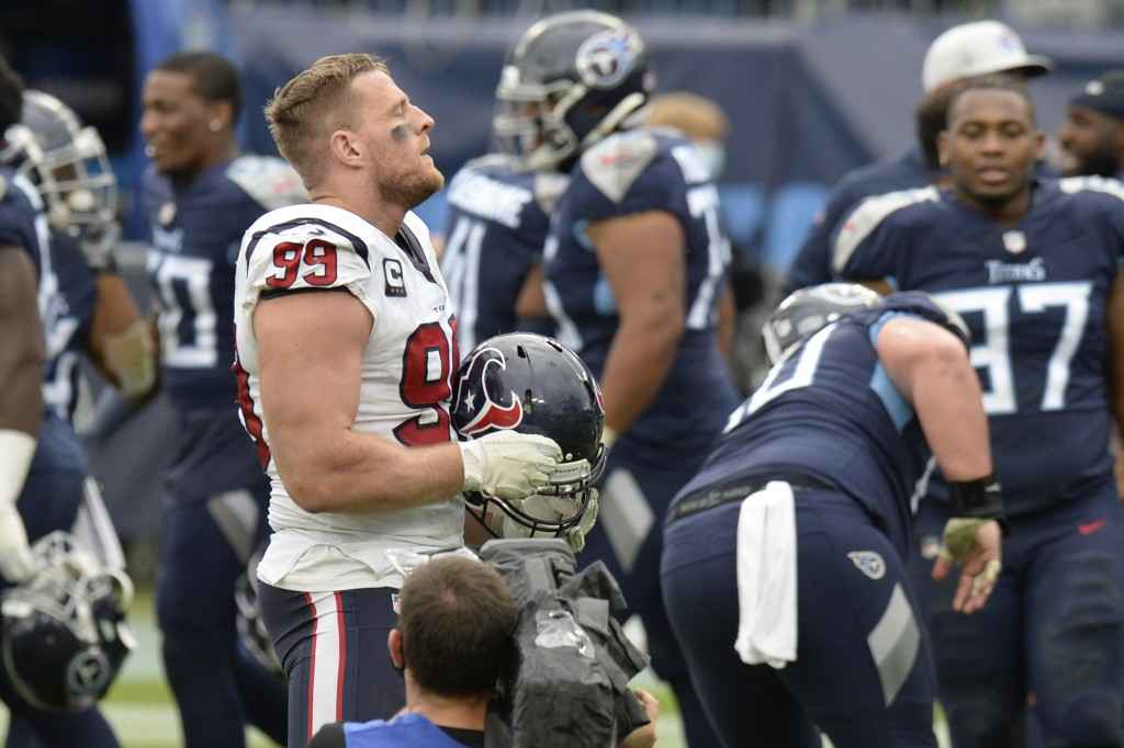 Houston Texans defensive end J.J. Watt (99) stands on the field as Tennessee Titans players celebrate after overtime of an NFL football game Sunday, O...