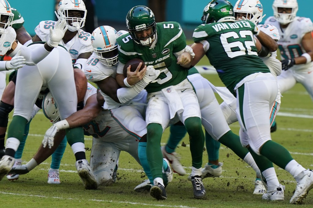 New York Jets quarterback Joe Flacco (5) is sacked by Miami Dolphins linebacker Sam Eguavoen (49), during the first half of an NFL football game, Sund...