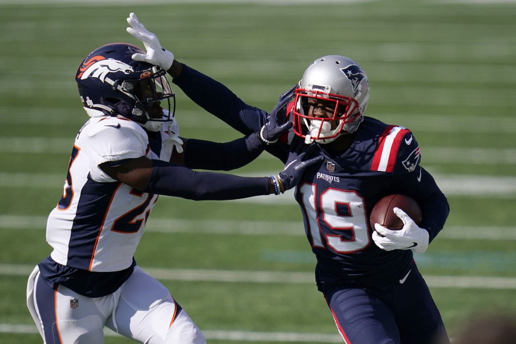 New England Patriots wide receiver Isaiah Zuber (19) tries to elude Denver Broncos cornerback Michael Ojemudia, left, in the first half of an NFL foot...