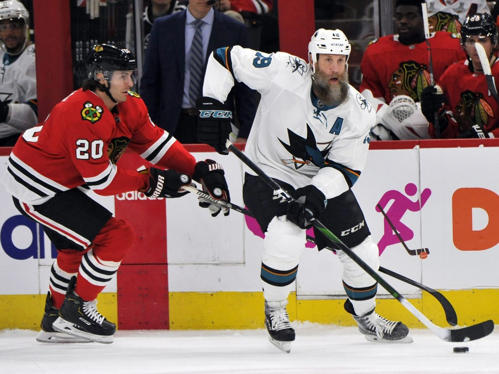 FILE - In this March 11, 2020, file photo, San Jose Sharks' Joe Thornton (19) moves the puck as Chicago Blackhawks' Brandon Saad (20) defends during t...
